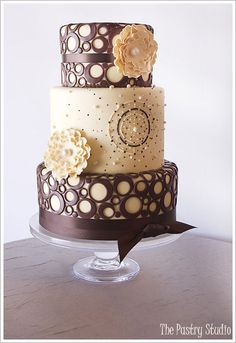 A fun and intricate wedding cake. I'm not a huge fan of circles on wedding cakes, but The Pastry Studio did an amazing job on this cake! Aren't those flowers lovely!