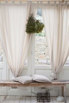 Catch a glimpse. Knotting curtains is a more casual way to pull them aside, letting light in and creating a easygoing atmosphere.