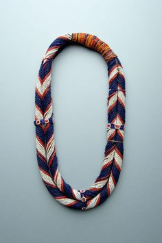 A beautiful necklace of two strands, i.e. rolls covered with glass beads of several colours, and tied together at the top. Nagaland (India): Konyak Naga people.