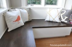 DIY wood topped bench banquette for eat-in kitchen with paneling and machine washable hand-painted pillows (no bench cushions = easy clean-up!)