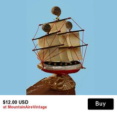 Sea Shell Tall Ship Home Decor   This charming seashell ship has Abalone shells for sails, wooden masts with red strings attached. The boat is in red, white, and blue and made of wood. It sets on a bigger shell and the masts are topped with snail shells. This is a really cute item from the 1950's. It may be tiny but it's look is very big and bold.  #modelship #shells #homedecor #abalone #ship #tallship #vintage #mountainairevintage