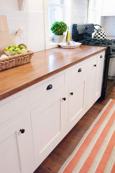 Wood counter top with white cabinets, stripe rug