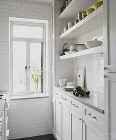 All white galley kitchen with subway tile and open shelves.