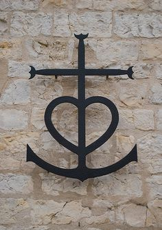 The Camargue cross on the wall of the church in Saintes-Maries-de-la-Mer, France.  The mixture of the 3 shapes of cross, heart and anchor are meant to symbolize faith, hope and love.