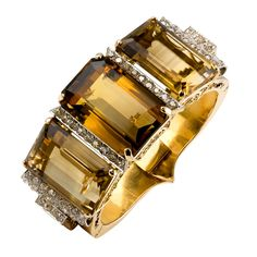 Impressive yellow gold & platinum bangle bracelet with diamonds and large smoky topaz , circa 1940s. It features three rectangular step cut smoky topaz stones, weighing a total of approx. 155.50cts, as well as very high grade round brilliant cut diamonds of approx. 4.00cts total weight.