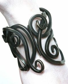 Natasha Wozniak, Baroque Wrought Cuff, $2,420.00  Blackened sterling silver has a hinge and clasp integrated into the design, so that it encircles the wrist. This bold bracelet is perfect for wearing with a business jacket, or short sleeves in summer. In order to get a proper fit, please measure the wrist circumference, and also measure the arm three inches above the wrist. Also indicate if the wrist is round in shape, or is more flat.