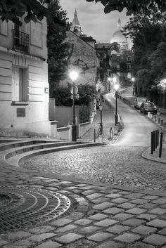 Ambiance nocturne sur la butte Montmartre vue depuis la place Dalida. Au loin se détachent les hauts du Sacré Cœur.