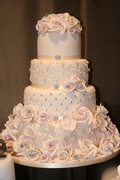 Traditional wedding cake with diagonal beading, ribbon and lots of roses.  Pretty cake.   ᘡղbᘠ