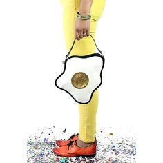 A fried egg shaped small handbag. The egg is made up of a pearly white base with a yellow yolk, all dripping in glitter.