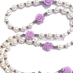 This simple, yet elegant Rosary features 6mm off-white pearls with light purple colored roses for the Our Father beads, along with purple seed beads in between and silver accents. Rosary features a be