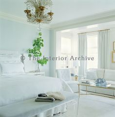 Duck-egg blue and palest dove-grey in the cloud-like master bedroom are accentuated by soft white carpets and bedding, a Lucite Anne Coyle bench and vintage Bagues chandelier