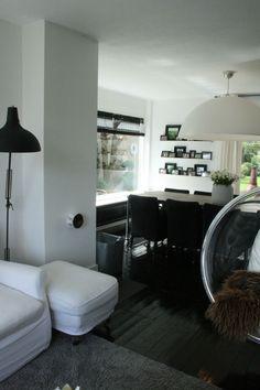 Koepellamp, zwart geschilderde vloer, witte fauteuil.