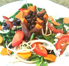 Sweet potato stuffed with beans surrounded with salad.