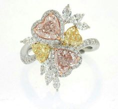 Pink and yellow heart cut diamond  ring surrounded  by colorless  diamonds