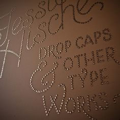 Thumb tacks - Print out the font you love and trace it on a canvas and then pin.