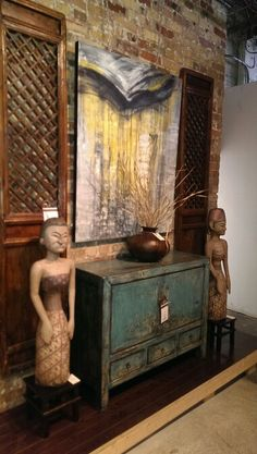 """Another treasure from the east has unfurled itself in our showroom. This solid poplar buffet has two doors opening into one cabinet & three drawers underneath 34""""H x 43""""W x 16""""D- $1195. It is adorned on both sides with original pieces of folk art from Papua New Guinea -$395 and solid elm doors from 1920s Shanxi China 17"""" W x 80"""" H-$450 each. The set is finished with an original canvas with rich acrylic textures 40"""" W x 49"""" H-$395 and a tin water condenser -$95."""