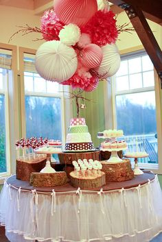 "table with cakes and huge pom pom ""bouquets"" extending from the ceiling"