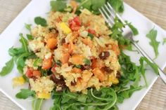 Quinoa salad with orange, yellow and red peppers, carrot, scallion, raisins, apricots, and almonds
