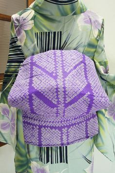 わずかに青みをおびた藤色に近いスモーキーな紫に、粋な矢羽根縞がふっくら鹿の子の本絞りで浮かび上がる名古屋帯です。