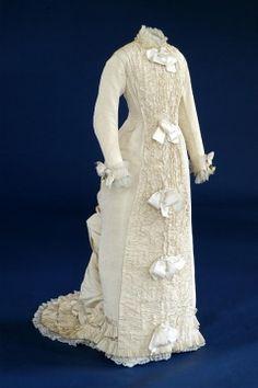 1888 cream silk wedding dress trimmed with white satin ribbon bows.
