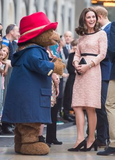 October 16, 2017— Kate Middleton met Paddington Bear at his namesake train station in London while wearing a knee-length pink dress by Orla Kielywith a black bow at the waist to set off her just-now visiblebaby bump.