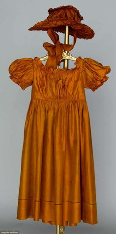 """Child's silk dress and hat, 1825-1830;  Rust China silk, short puff sleeves, W 20"""", L 29"""", matching ruched hat on cane frame, Wd 12"""""""