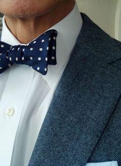 Dark grey herringbone tweed jacket, white shirt, navy bow tie with white polka dots