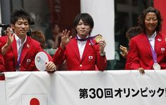 金メダルを披露しながら沿道の声援に応える内村選手(中央)