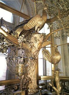 die berühmte Pfauenuhr wurde von dem englischen Mechaniker James Cox gebaut. 1780 erwarb sie Fürst  Grigorij Potjomkin diese Kuriosität, um sie seiner Geliebten Katharina der Grossen zu schenken. Das Zifferblatt befindet sich im Hut eines Pilzes vor dem Baumstumpf auf dem der Pfau sitzt. Wenn die Uhr schlägt, schlägt der Pfau sein Rad, die Eule im Käfig dreht den Kopf und blinzelt mit den Augen und der Hahn kräht. Eremitage