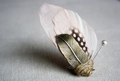 Feathers aren't just for fascinators. With their intricate designs, subtle shading and touchable texture, they can look surprisingly chic on a lapel. This Pomp & Plumage boutonnière is a great example.  Zelma Rose Dry Goods