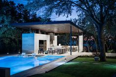 This Poolside Living Room And Kitchen Sits Under A Large Floating Canopy This modern steel, limestone, and wood outdoor pavilion has a living room, an outdoor kitchen with a bbq, and a dining area.