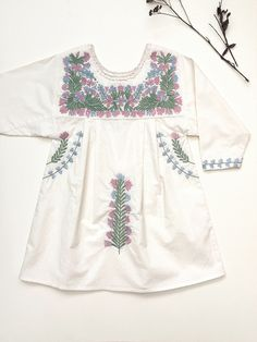 'PATTIE' DRESS - ALABASTER WITH MULTI-COLOURED PASTEL EMBROIDERYTaking the comfort and practicality of traditional 1970s Mexican embroidered dresses and combining with a heritage Swedish folk i...
