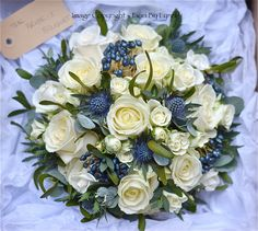 This blue and ivory bouquet contains ivory roses, thistles, navy berries, eucalyptus and mistletoe.
