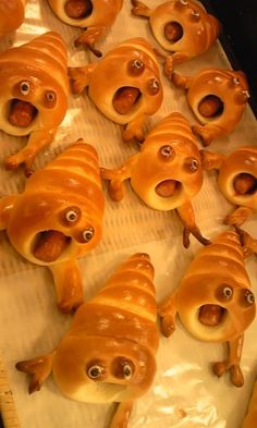 Pigs in a blanket for Halloween dinner. Screamers!!! Sooooo cute!! (Update: The recipe for this is still yet to be found, however, as the bodies look to be made from pretzel dough, I did a search and found this: http://www.mrsfields.com/blogs/blog/tag/pigs-in-a-blanket-recipe/ It's a recipe that, with a few tweaks and practice, may do the trick! Hope that helps, folks!)