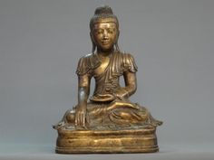 Bouddha Maravijaya au beau visage souriant. Il est assis en padmasana, les mains en position de prise de la terre à témoin, vêtu de la robe monastique aux plissés ondulant d'une beauté intemporelle. Sculpture en bronze à la cire perdue - patine mordorée lustrée. Birmanie (royaume de Mandalay) - début du 19e siècle. Hauteur : 45 cm