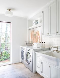 White and bright laundry room with white subway tile, white cabinets, and steel windows in traditional modern farmhouse in California by Steve and Brooke Giannetti in C Magazine