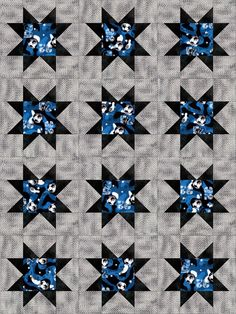 Quilting kit features black and white soccer balls scatter about on a blue, black and white camouflage background. On this print will also be scattered white stars, the numbers 32 and 52 outlined in w