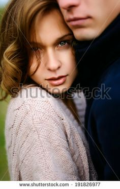 Beautiful girl in the arms of her boyfriend looking at the camera by Aliaksandr Khmialiou, via Shutterstock