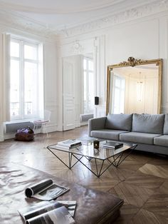 modern. minimal living room. grand mirror. brown leather. parquet floors. white walls. decorative molding. modern meets classical.