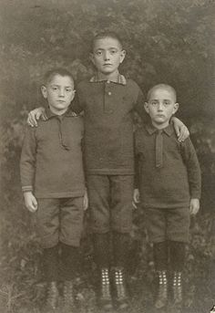 August Sander   German, about 1925   This photograph of three boys was typical of Sander's commercial practice. Originally created as an object to exchange with family members or insert in an album, the small-format postcard intensifies personal contact with the solemn young subjects, whose dark clothing blends with the dense foliage in the background