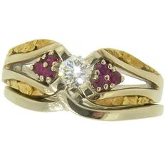 Stunning diamond center stone surrounded with gorgeous Alaskan gold nuggets and Rubies fancily arranged in 14kt white gold. Custom Engagement Rings ~ 907-456-4991 ~ Alaskan Gold Rush Fine Jewelry ~ Fairbanks, AK.