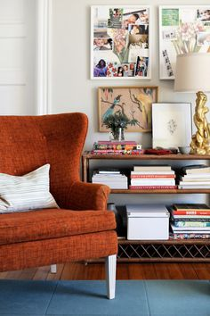 burnt orange arm chair, golden lamp, books, and art