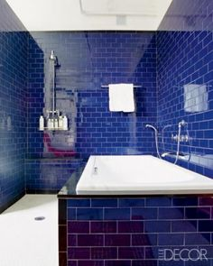 Royal blue subway tile is offset by the white porcelain and grout of the bathroom