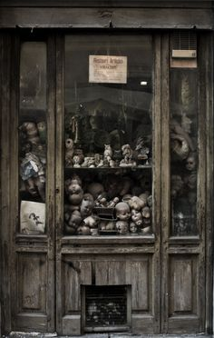 Old Shop Window - Dolls Heads & Owls = CREEPY- wouldn't this be fun for a Halloween party with a china cabinet?!