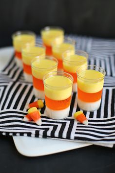 1 sm box orange Jell-O (3 oz) 3 envelopes Knox unflavored gelatin 7 oz. sweetened condensed milk  2 C water  1 C vanilla vodka  yellow food coloring 20 tall shot glasses