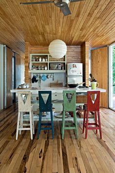 Cozinha compacta | Para aquecer os interiores, teto, piso, paredes e até as portas foramrevestidos com réguas de madeira tratada (Foto: Divulgação)