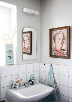 "Sneak Peek: Jenny Brandt & Jens Grönberg. ""We have a tiny bathroom. Jens bought the picture on the wall at an antique store. We call her the principal. She gives us a well-deserved stern look as we get ready in the morning. We can't be joking around all the time, and she reminds us of that."" #sneakpeek"