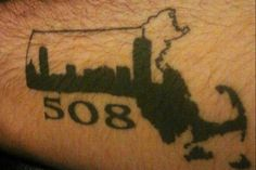 Mass state and area code tattoo with Boston skyline.