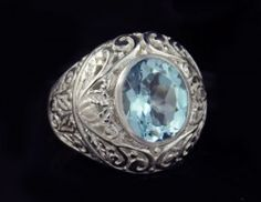 Handmade Sterling Silver Blue Topaz Ring floral intricate detailing Made in Bali Size 7 Oval cut blue topaz ( 10mm wide) Band measures 7mm wide tapering to 5mm at the back 10.6g Hallmarked Lydia Lerner Stamped 925