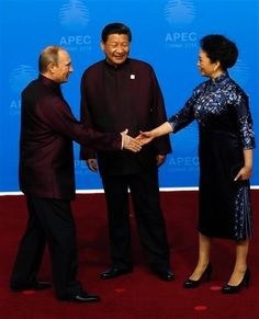 In this photo taken Monday, Nov. 10, 2014, Russia's President Vladimir Putin, left, shakes hands with Chinese first lady Peng Liyuan as Chinese President Xi Jinping, center, watches before a dinner hosted for APEC leaders at the Beijing National Aquatics Center in Beijing. It was a warm gesture on a chilly night when Vladimir Putin wrapped a shawl around the wife of Xi Jinping later in the evening while the Chinese president chatted with Barack Obama. The only problem: Putin came off looking…